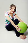 A young woman with a green exercise ball