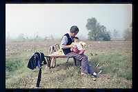 An elderly Chinese peasant plays with her grandson on her farmland at a village in Jiangsu province, China, 1998.
