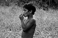 An indigenous boy sucks honey from a honeycomb of wild bees, deep in the Amazonian jungle in Brazil, 25 April 2004. Amazonia is the world's largest dense tropical forest area. Since the 16th century the original indigenous people have been virtually pushed away or exterminated. The primal ancient unity between tribes and the jungle ambient has changed into a fight between the urban based civilization and the jungle enviroment. Although new generations of white and mestizo settlers have not become adapted to the wild tropical climate and rough conditions, they keep moving deeper into the virgin forest. The technological expansion causes that Amazonia is changing rapidly.