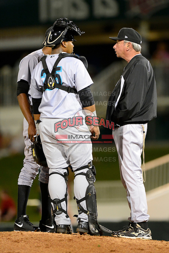 Jupiter Hammerheads pitching coach Joe Coleman #15 (right) talks with pitcher Jose Urena #34 behind catcher Wilfredo Gimenez #25 during a game against the Fort Myers Miracle on April 9, 2013 at Hammond Stadium in Fort Myers, Florida.  Fort Myers defeated Jupiter 1-0.  (Mike Janes/Four Seam Images)