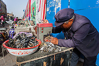 Chinese street vendor making spare keys with a machine in Datong, China