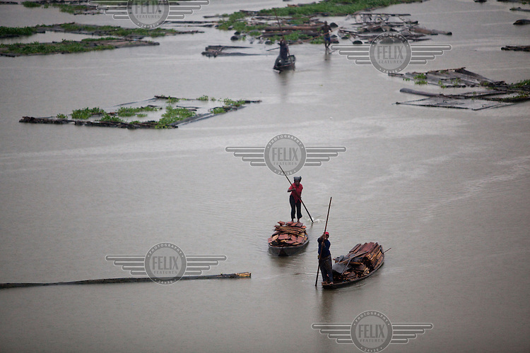 People carry scrap wood in canoes to sell in the Ebute Metta neighbourhood. This is the principal wood milling and timber supply area for the city. Timber is floated in rafts from north and east of Lagos and then milled and sold.