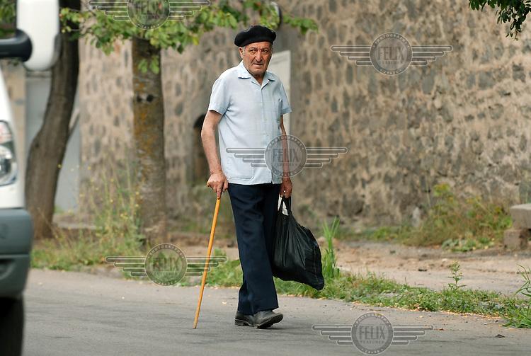 A man walks with his shopping through the town of Goris.