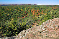 Granite bluffs overlook a mixed forest, typical of the southern Canadian Shield, along the Lookout Trail in Algonquin Provincial Park, northern Ontario, Canada. The mixed forest shown here includes balsam fir, eastern white pine plus sugar and red maple trees with autumn foliage.