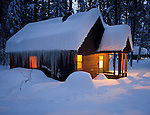 Okanogan County, WA<br /> Warm light from a snow covered cabin at dusk, winter