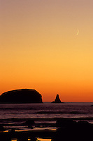 Crescent moon rising above sea stacks during a spectacular orange hued sunset, Olympic National Park, Coastal Strip, Olympic National Park, WA.