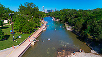 Aerial drone view of the west end of Barton Springs Pool all the way to the far east side. This view provides a picture-perfect perspective view from above of the pool as swimmers lounge in the emerald green springs and shun the blistering Austin, Texas heat, reaching well over the 100s during the annual spring and summer seasons.