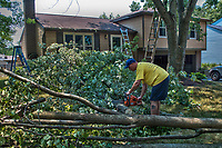 Neighbor uses his chain saw to cut up a section of tree that fell across the house of a friend across the street in Friday night's hurricane-force thunderstorm. Most residents in Westerville, Ohio, had their power restored within hours after the storm. The rest of the state had as many as 1 million people without power with some not expected to get it back before next weekend.