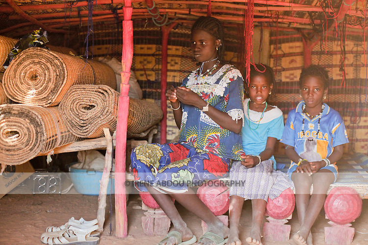 In the Fulani village of Jolooga in northern Burkina Faso, a family sits on a traditional bed in a house made of handwoven straw mats supported by thin sticks of wood.  Additional straw mats serve as both mattress and decoration.