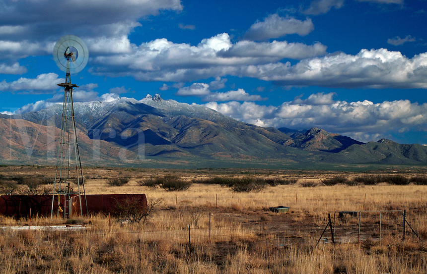A ranch windmill on a desert plain, with the Dos Cabezas montains in the background. Arizona.