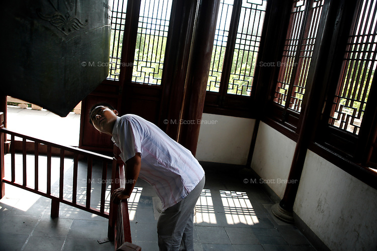 A man looks at a Buddhist bell in a temple in Suzhou, China.