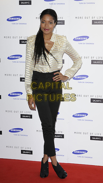 NAOMIE HARRIS.attends the launch of the Samsung Galaxy S Smartphone held at Altitude Bar, London, England, UK, .June 15th, 2010. .full length gold cream striped sheer blouse top shirt hand on hip black trousers ankle boots booties .CAP/CAN.©Can Nguyen/Capital Pictures.