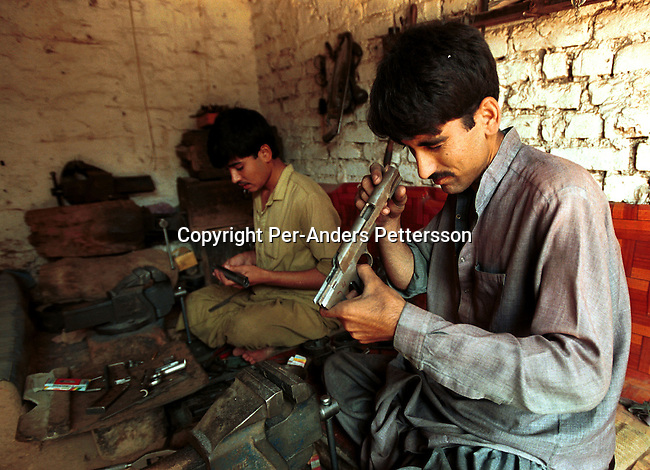 Naeen Baheam, age 20, is checking a copy of a Chinese pistol with his co-worker Hakeen Rahman, age 15 on September 22, 2001 in Darra, a village about 40 kilometers south of Peshawar, Pakistan. They work in an underground weapons factory. These factories have made copies of weapons for over one hundred years and they are used in conflicts in Afghanistan, The Balkans and Kashmir and other areas. These weapons are also smuggled into Afghanistan to the Taleban movement..Photo: Per-Anders Pettersson/ Grazia Neri......