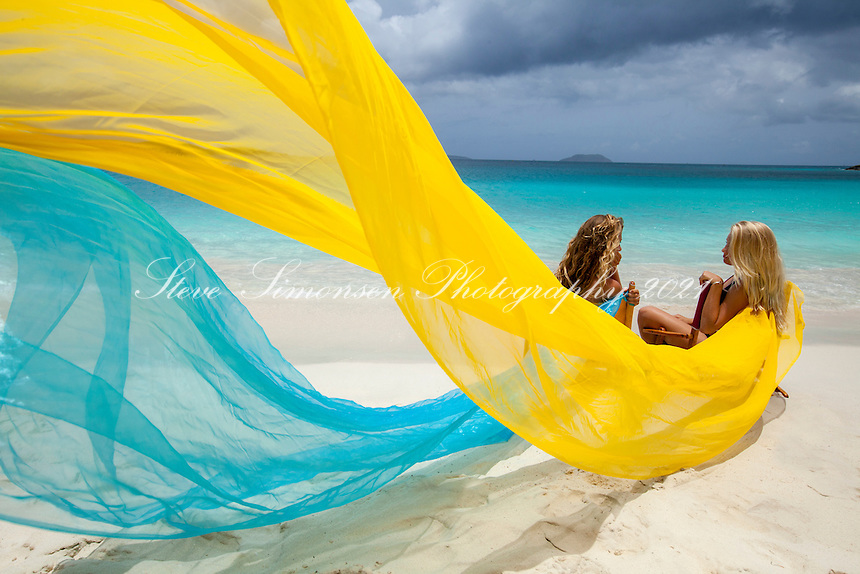 Girls in beach chairs with scarves blowing in the wind
