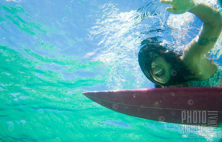 A local Asian woman paddling on her surfboard at Waimea Bay