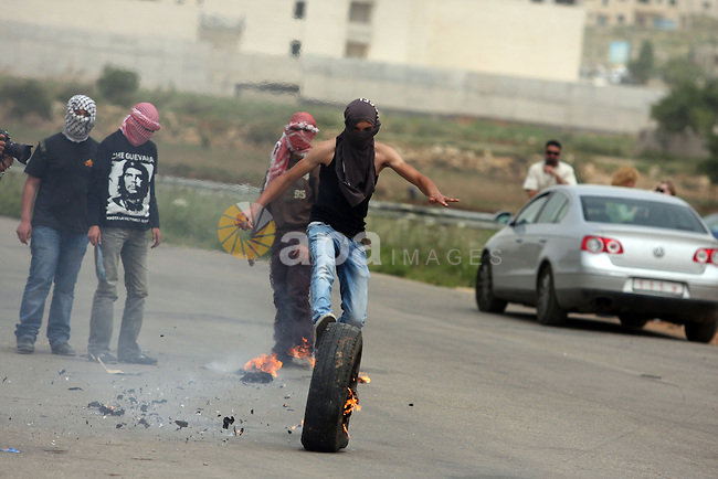 "Protesters light a rubber tyre and kick it towards a fence during a demonstration outside Ofer military prison near the West Bank city of Ramallah on May 1, 2012 in a show of support for prisoners held in Israeli jails. Clashes erupted between stone-throwing youths and the Israeli army, who fired tear gas, rubber bullets and a foul-smelling liquid known as ""skunk"" to break up the demonstration. Photo by Issam Rimawi"