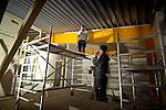 NIEUWEGEIN - In Nieuwegein starten medewerkers van aannemersbedrijf Kwakkenbos uit Harmelen de bouw van de openbare school De Toonladder, 's ochtends op met koffie en een peuk. Om zeven uur precies gaat men de school binnen, om radio's, machines en lampen aan te zetten, batterijen op te laden, en een planning te maken voor de dag. Wegens het slechte weer arrivern de mannen die buiten aan het dak werken, pas later die dag. Vanwege de kou binnen, dragen de meeste mannen mutsen op het hoofd en handschoenen. De bouw van de school gaat ongeveer 2,6 miljoen euro kosten. COPYRIGHT TON BORSBOOM