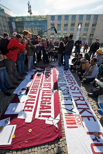 Seit Mittwoch den 9. Oktober 2013 befinden sich in Berlin etwa 2 dutzend Fluechtlinge vor dem Brandenburger Tor erneut im Hungerstreik.<br />Die Fluechtlinge fordern die Anerkennung ihrer Asylantraege und wollen den Hungerstreik so lange weiterfuehren bis ihre Forderung erfuellt wird.<br />Ein erster Hungerstreik im Winter wurde nach mehreren Wochen erfolglos beendet.<br />Hier: Am 6. Tag des Hungerstreiks, Montag den 14. Oktober 2013, verkuenden die Fluechtlinge, dass sie ab sofort zusaetzlich auch in einen Durststreik treten.<br />14.10.2013, Berlin<br />Copyright: Christian-Ditsch.de<br />[Inhaltsveraendernde Manipulation des Fotos nur nach ausdruecklicher Genehmigung des Fotografen. Vereinbarungen ueber Abtretung von Persoenlichkeitsrechten/Model Release der abgebildeten Person/Personen liegen nicht vor. NO MODEL RELEASE! Don't publish without copyright Christian Ditsch/version-foto.de, Veroeffentlichung nur mit Fotografennennung, sowie gegen Honorar, MwSt. und Beleg. Konto:, I N G - D i B a, IBAN DE58500105175400192269, BIC INGDDEFFXXX, Kontakt: post@christian-ditsch.de.<br />Urhebervermerk wird gemaess Paragraph 13 UHG verlangt.]