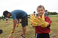 NWA Democrat-Gazette/FLIP PUTTHOFF <br /> FRUIT TAKING ROOT<br /> Levi Newman, 5, admires his work gloves while his dad, Matt Newman, plants a fruit tree Saturday June 17 2017 at the new location of the Samaritan Community Center garden at South Eighth Street and Pleasant Grove Road in Rogers. The garden is being moved in phases from its current location at the Samaritan Community Center in Rogers to the larger space, said Debbie Rambo, executive director of Samaritan Community Center. Volunteers planted 50 apple, pear and persimmon trees Saturday and a deer-proof fence was erected. The Fruit Tree Planting Foundation donated the trees, said Rico Montenegro, with the The Fruit Tree Planting Foundation.