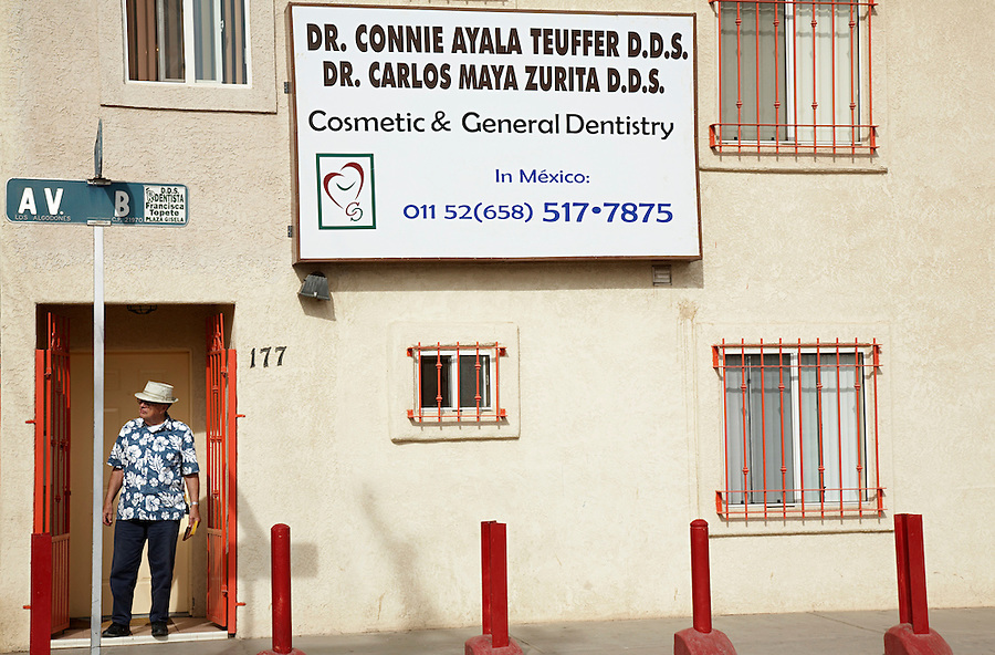 Tourist standing in front of dentist's office, Los Algodones, B.C, Mexico.
