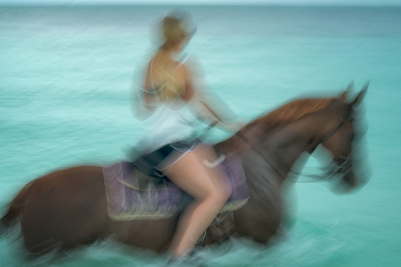 Woman riding horse in water. Turks and Caicos. Providenciales