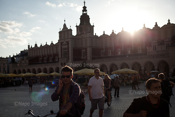 KRAKOW, POLAND, SEPTEMBER 13, 2011:.Tourists and locals are passing by in the evening at the Old Town's main square, with the Sukiennice shopping arcade in the background..(Photo by Piotr Malecki / Napo Images) ..KRAKOW, 9/2011:.Stary Rynek..Fot: Piotr Malecki / Napo Images