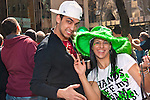 MARCH 17, 2011 - MANHATTAN: Happy young man and woman wearing big green hat and waving at viewer, at Saint Patrick's Day Parade on 5th Avenue and E 51st, with St. Patrick's Cathedral across the street in background. NOTE: slight motion blur due to man moving thumb (EDITORIAL USE ONLY)