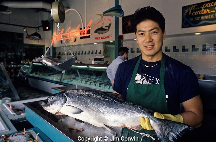 Fishermens Terminal with man holding salmon in store smiling at camera Seattle Washington State USA
