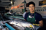Fishermens Terminal with man holding salmon in store smiling at camera Seattle Washington State USA