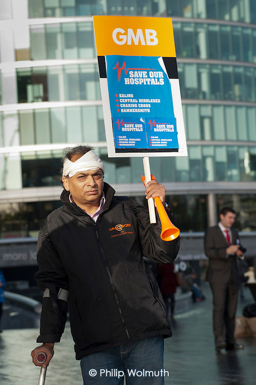 Man with a bandaged head protests outside the Greater London Assembly over proposed A&E closures at four London hospitals.