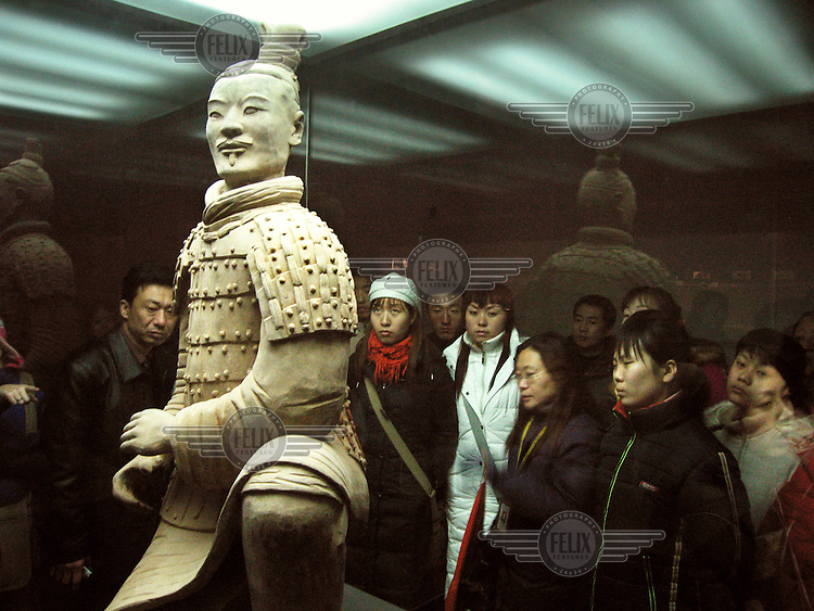 Chinese tourists gather round to look at a 2,000 year old terracotta sculpture of a warrior at its excavation site in Xi'an.  The Qing Dynasty burial site was discovered in 1974 by several local farmers while drilling a well.  Containing 6,000 figures of warriors and horses in battle array, the location is a designated UNESCO World Heritage Site. ..