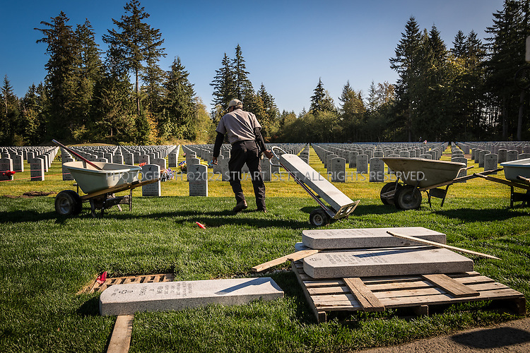 9/30/2016-- Tahoma National Cemetery, Kent, WA, USA<br /> <br /> Here: In a seperate part of the Tahoma National Cemetery, cemetery employees continue the daily work of burying veterans and their spouses.<br /> <br /> James Lindley, 34, an undertaker and US Marine Corp Veteran, works at the Columbia Funeral Home in Seattle, Washington and has taken it upon himself to process the remains of indigent veterans and ensure their remains are placed in Tahoma National Cemetery in nearby Kent, WASH. The veterans are given full military funerals with active service members as well as volunteers who stand-in for unavailable next-of-kin, accepting the folded flags provided by the Veterans Administration.<br /> <br /> On this day, with the help of Mr. Lindley, the remains of 4 veterans were interred at the Tahoma National Cemetery: <br /> <br /> Richard Fesler, born 1951, died 2014. US Army Veteran<br /> Rocky Stallone, born 1951, died 2014. Marine Corps veteran<br /> Russell Ristow, born 1944, died 2014. US Army veteran.<br /> Wayne Roberts, Born 1937, died 2014. US Navy veteran.<br /> <br /> <br /> Credit: Stuart Isett for The Wall Street Journal. <br /> VETBODIES<br /> <br /> &copy;2016 Stuart Isett. All rights reserved.