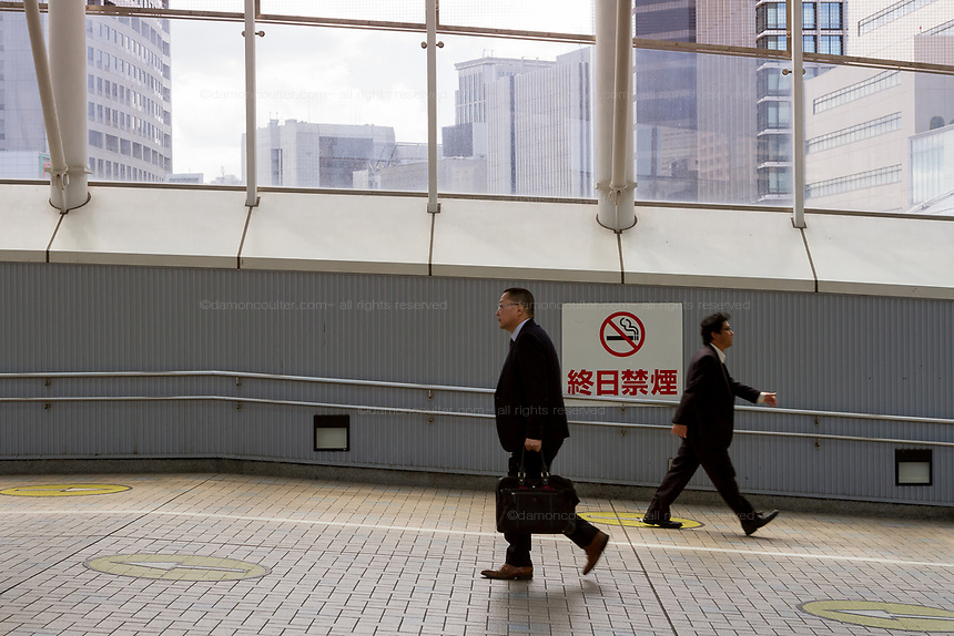 Two Japanese salarymen walk past a No Smoming sign in Tamachi station, Tokyo, Japan. Monday April 15th 2019
