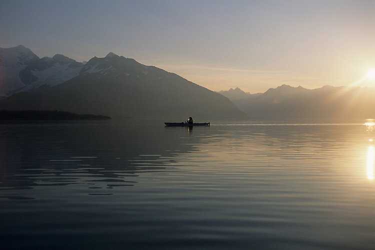 The sun rises above the Chugach Mountains behind a sea kayaker paddling in Prince William Sound's Harriman Fjord, north of Whittier, Alaska.