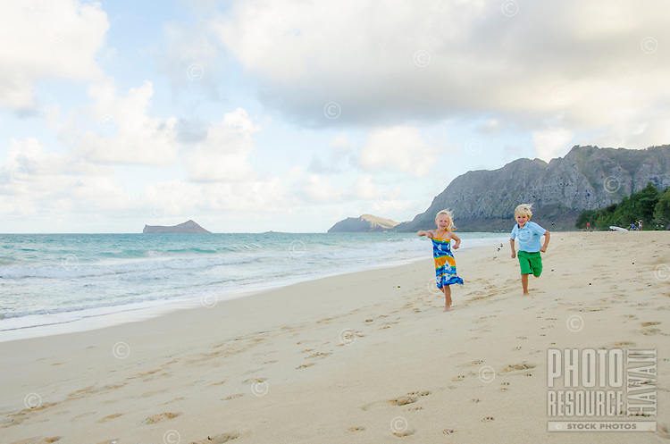 Two children running on Waimanalo Beach, O'ahu, with Rabbit (or Manana) and Bird (or Kaohikaipu) Islands in the distance.
