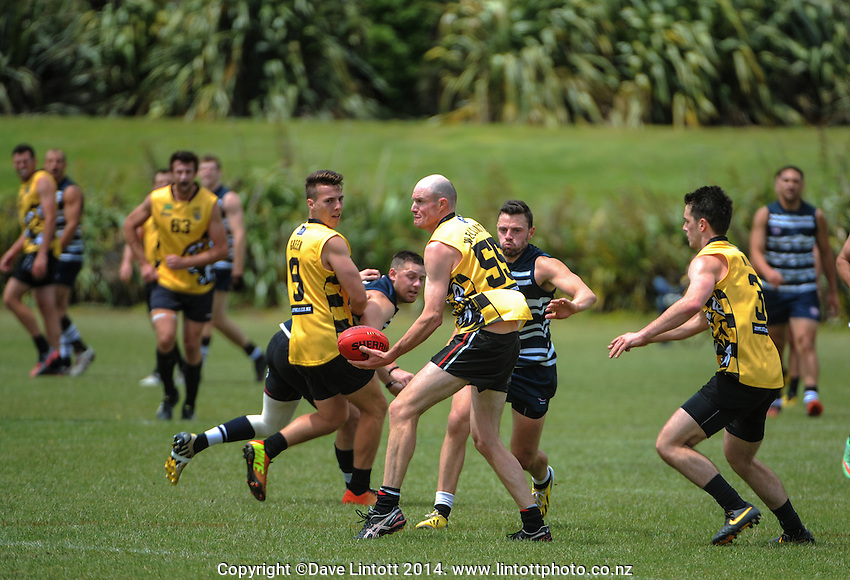 Jason Cox looks for support during the Wellington Australian Rules Football National Provincial Championship final match between the Wellington Tigers (black and yellow) and Auckland Buccaneers (blue and white) at Hutt Park, Wellington, New Zealand on Saturday, 6 December 2014. Photo: Dave Lintott / lintottphoto.co.nz