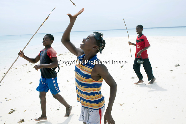 PEMBA, TANZANIA - DECEMBER 7 : Hamissi Usi (r), age 15, plays on a remote island with his friends on December 7, 2010 on Pemba, Tanzania. He works as a fisherman. He doesn't go to school but lives with his parents and siblings in the small village of Tumbe. (Photo by: Per-Anders Pettersson)