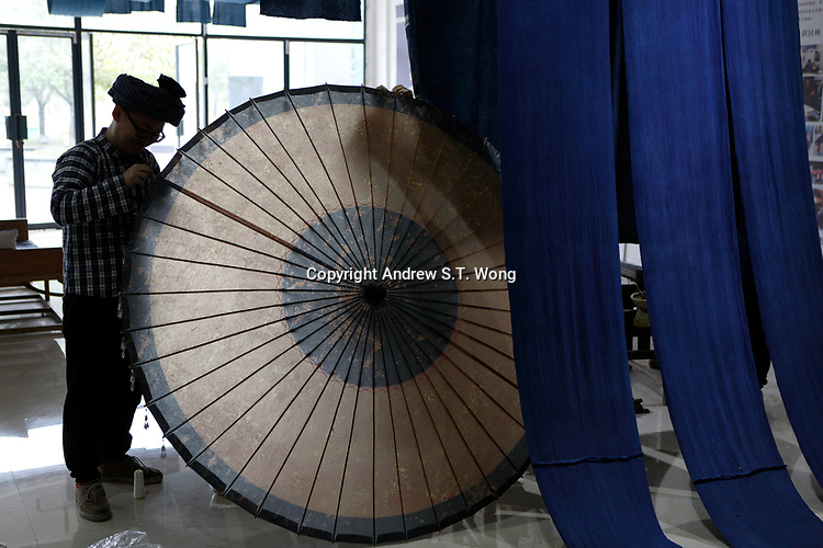 Ethnic Bouyei fashion designer Wei Xianglong decorates a traditional oil paper parasol at his studio in Duyu, Guizhou Province, 2018.