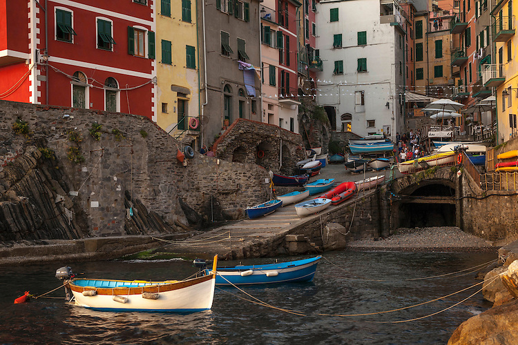Stacked buildings & boats seem to tumble down to the sea at Riomaggiore