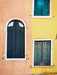Pastel orange and yellow wall with windows, along a back alley inVenice, Italy.