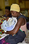 Mother and baby on a bed in a ward at Kigali District Hospital, Kigali, Rwanda.