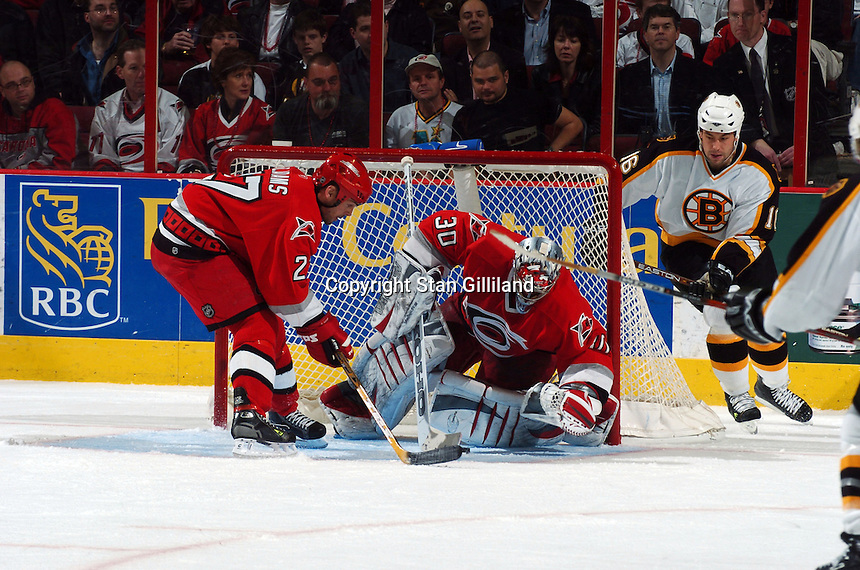 Carolina Hurricanes' goaltender Cam Ward makes a save helped by teammate Craig Adams as the Boston Bruins' Marco Sturm, right, watches during their game at the RBC Center in Raleigh, NC Wednesday, March 1, 2006. The Hurricanes won 4-3...