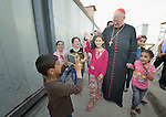 Cardinal Timothy Dolan, the archbishop of New York, is accompanied by children as he walks through a camp for internally displaced families in Ankawa, near Erbil, Iraq, on April 9, 2016. Dolan, chair of the Catholic Near East Welfare Association, led a delegation of church leaders to Iraqi Kurdistan in order to visit with Christians and others displaced by ISIS.