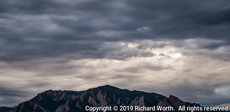 Instead of brilliant orange and red this sunset is in varying shades of gray over the foothills west of Boulder, Colorado