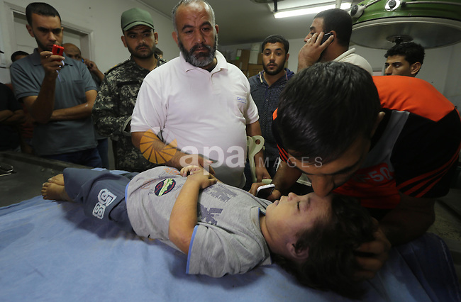 People stand around the body of a three-year-old Palestinian girl who was killed after her house was brought down by an Israeli air strike in Gaza early on October 11, 2015. An Israeli air strike on a Hamas target in the Gaza Strip on Sunday brought down a nearby house killing a Palestinian woman and her daughter, hospital officials said, as a wave of violence in the region triggered fears of wider escalation. Photo by Mohammed Asad