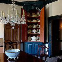 A painted corner cabinet in the dining room displays a porcelain dinner service
