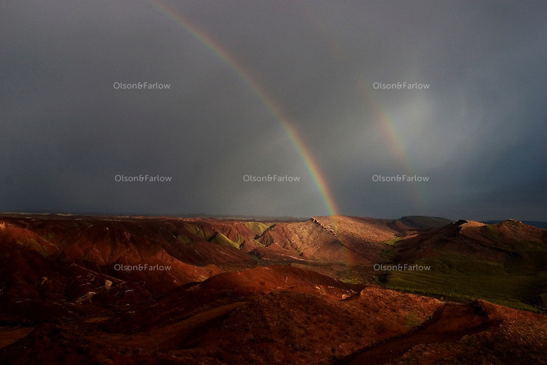 Aerials of the hills around Halls Creek show a stark landscape with two rainbows reflected as a storm blankets the region.