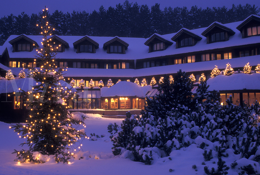 AJ4687, lodge, inn, resort, Trapp Family Lodge, winter, Christmas, X-mas, Xmas, Vermont, The snow covered Trapp Family Lodge is decorated with lights in the evening for the Christmas holiday season in Stowe in Lamoille County in the state of Vermont. An evergreen tree is decorated with tiny white lights in the foreground.