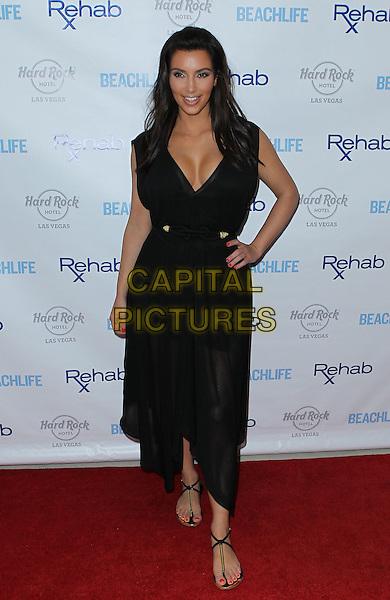 Kim Kardashian.hosts Rehab Sunday at Paradise Beach at the Hard Rock Hotel and Casino, Las Vegas, Nevada, USA..3rd June 2012 .full length black dress sheer cleavage belt hand on hip.CAP/ADM/MJT.© MJT/AdMedia/Capital Pictures.