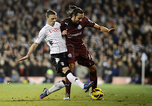 10.12.2012 London, England. Chris Baird of Fulham  and Jonas Gutierrez of Newcastle in action during the Premier League game between Fulham and Newcastle United from Craven Cottage.